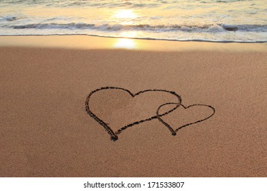 Hearts in the sand on the beach at sunset.