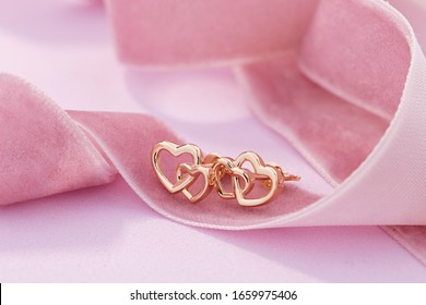 Hearts shape rose gold stud earrings on pink background. Romantic  jewelry. Advertising still life product concept for Valentines Day