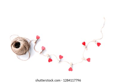 Hearts strung on a rope on a white background. A ball of brown thread. Symbol of love, friendship, loyalty. Family holidays. Valentine's Day. Copy space.