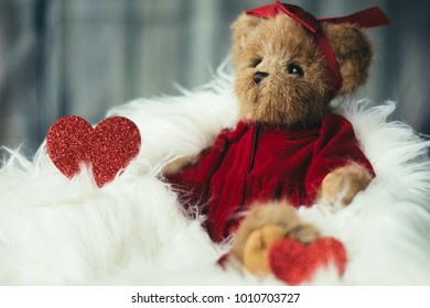 Hearts and a stuffed bear in fluffy fur with red dress. Valentines day background.