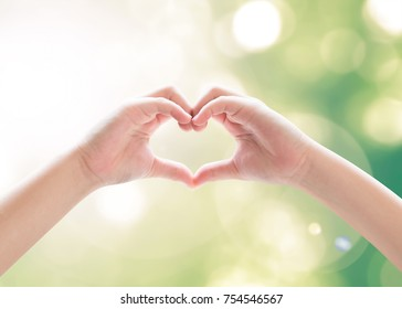 Heart-shape hand gesture of kid's body language for children's love, peace, kindness and world humanitarian aid day, CSR concept. Hand isolated on sky with green bokeh and sun flare