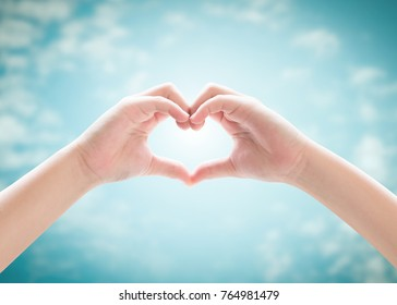 Heart-shape hand gesture of kid's body language for children's love, peace, kindness, csr charity donation, and world humanitarian aid concept. Hand isolated on blur blue sky with cloud