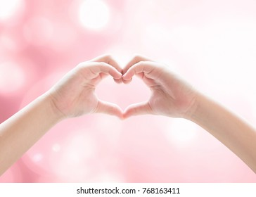Heart-shape hand gesture of kid's body language for children's love, peace, kindness, csr charity donation and world humanitarian aid concept. (Hand isolated on pink bokeh background and sun flare)