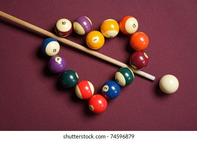heart-shaped billiard balls with cue ball and stick
