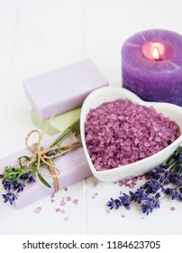 Heart-shaped bowl with sea salt, candle, soap and fresh lavender flowers on a wooden  background