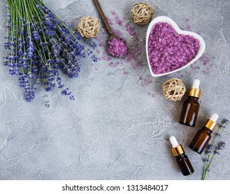 Heart-shaped bowl with sea salt and fresh lavender flowers on a concrete background