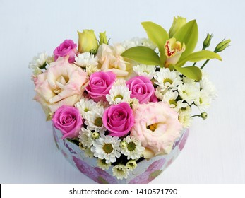 heart-shaped box with fresh flowers: green Orchid, white chrysanthemums, pink roses, pink eustoma, chrysanthemums like daisies, close-up on white wooden table with blurred background