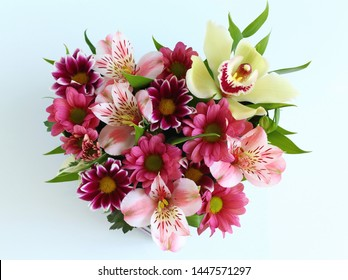 heart-shaped box with fresh flowers: green Orchid, pink chrysanthemum, variegated chrysanthemum, pink alstromeria, green close-up on a white table with a blurred background