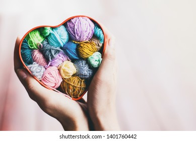 Heart-shaped box with knitted multi-colored skeins of yarn in hands on wooden background. Crochet and knitting. Women's working space.