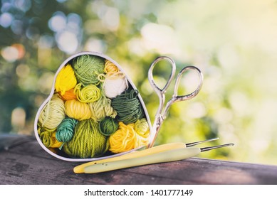 Heart-shaped box with knitted multi-colored skeins of yarn,crochet hooks , scissors on wooden background in the garden on spring day. Crochet and knitting. Women's working space.