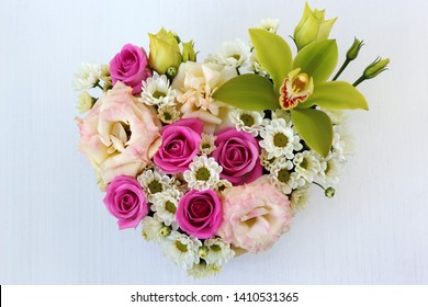 heart-shaped box on a white wooden table close-up, top view, with fresh flowers: green Orchid, pink roses, pink eustoma, white chrysanthemum, greens with blurred background