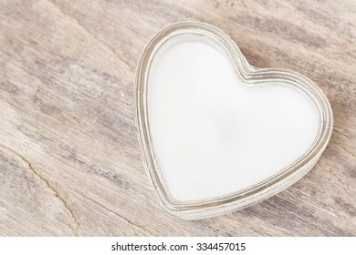 Heart-shaped candle on a wooden floor abstract style.
