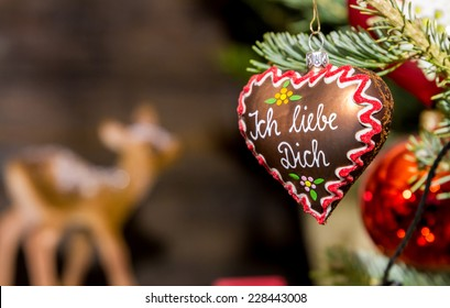 """Heart-shaped Christmas ornament at a Christmas Market, depicting a gingerbread heart with the words """"I love you"""" in German language"""