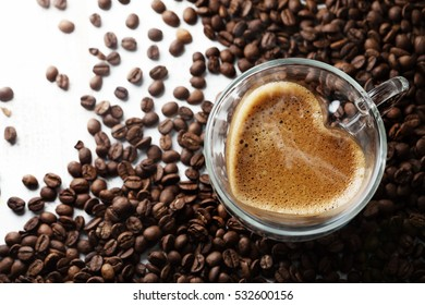 Heart-shaped coffee cup on wooden background with coffee beans