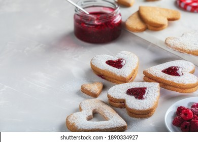 Heart-shaped cookies on light gray background with copy space. The middle of the cookies are filled with raspberry jam and sprinkled with powdered sugar. Valentine's Day biscuits making process.