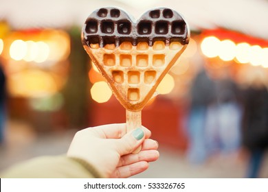 Heart-shaped freshly baked waffle in the hand