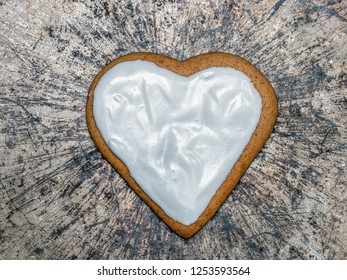 Heart-shaped gingerbread cake with white icing on metal scratched plate surface