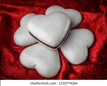 Heart-shaped gingerbread cakes with white icing on red fabric