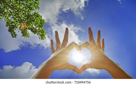 Heart-shaped hand gesture, Hands creating a heart with the sun in the middle on the beautiful sky background