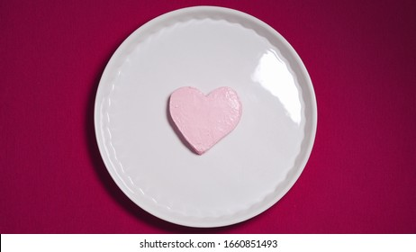 Heart-shaped ice-cream in white plate is melting on pink background. Sad Alone Valentine's. Top view.