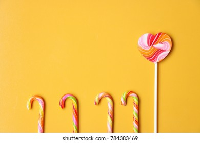 Heart-shaped lollipops and colorful candy canes on Amber color background.