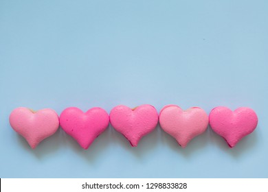 heart-shaped macaroons on blue background.Valentine's Day. Pink gift tied with rosy ribbon and macaron macaroon cookie on pink heart background top view. Valentines Day, 8 March, Womens Day, Birthday,