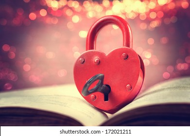 Heart-shaped padlock with key on open book