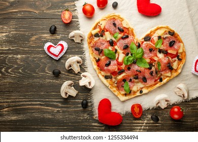 Heart-shaped pizza, Valentine's Day. With vegetables. A concept of tasty and healthy food with love. Free-lay
