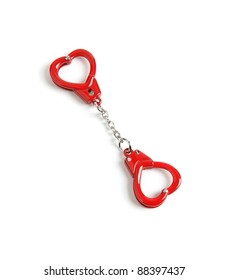 Heart-shaped red handcuffs isolated on white background