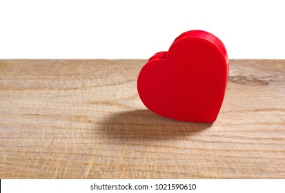 Heart-shaped red plastic box on an old wooden surface