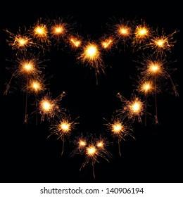 heart-shaped sparklers on black background