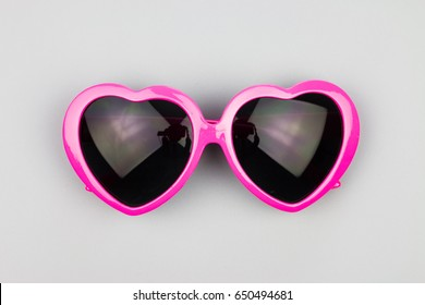 Heart-shaped sunglasses on a gray background
