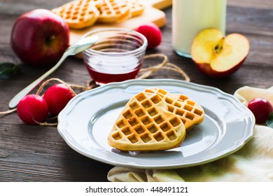 Heart-shaped waffles on a rustic wooden background