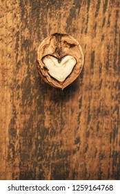 Heart-shaped walnut on a wooden background