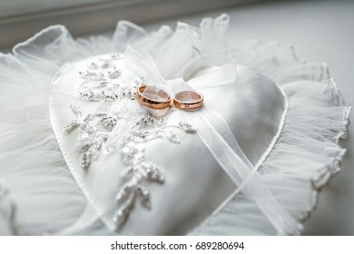 Heart-shaped white pillow with lace and wedding gold rings. Front side