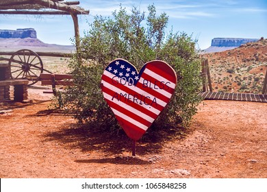 """A heart-shaped wooden sign representing the american flag with the inscription """"God bless America"""" in Monument Valley Navajo Tribal Park, Arizona. National and patriotic concept"""