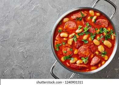 hearty beans stew with sausages, herbs and spices in tomato sauce in a metal casserole on a concrete table, fasolka po bretonsku, polish cuisine, view from above, flatllay, copy space