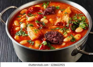hearty Fabada Asturiana Bean Stew with chorizo, bacon and blood sausages in a metal casserole on a black wooden table, spanish cuisine, horizontal view from above, close-up