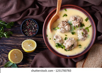 hearty Greek Meatball Soup - Giouvarlakia, Youvarlakia in Egg lemon sauce in a earthenware bowl on a wooden table with spoon, view from above, close-up, flatlay