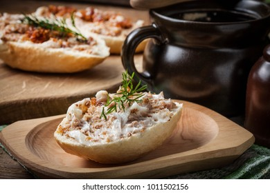 Hearty lard with greaves in a rustic stoneware pot served with fresh bread on a rustic wooden table. Dark light.