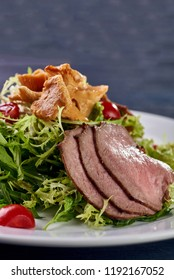 A hearty nice salad for the festive table. Slices of salted meat, bacon, beef, veal, pork from oven, meat sausage, ham. Appetizer from greenery, arugula, mushrooms chanterelles and cherry tomatoes.