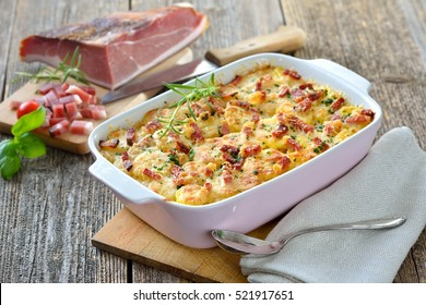 Hearty Potato-Gratin mit Parmesan-Käse, Sahne und köstlich gepökeltem Speck aus Südtirol, frisch aus dem Ofen auf einem Holztisch serviert