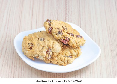 Hearty raisin cookies put on a white plate. The background is tiled flooring mimics wood.