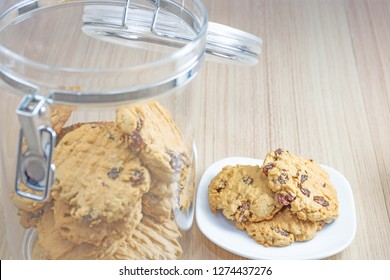 Hearty raisin cookies put on a white plate. Some of the cookies in the cookie jar lid off. The background is tiled flooring mimics wood.