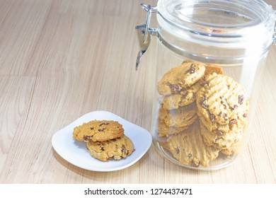 Hearty raisin cookies put on a white plate. Some of the cookies in the cookie jar. The background is tiled flooring mimics wood.