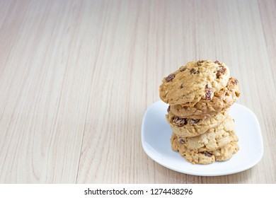 M้้any hearty raisin cookies stacked on a white plate. The background is tiled flooring mimics wood.