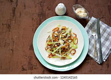 Hearty salad with fresh green radish, boiled beef, crispy fried onions and eggs. Served with mayonnaise. Top view.