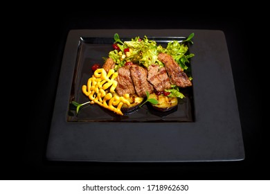 A hearty salad of juicy beef with herbs, corn, stewed zucchini and red paprika. Hearty dish on a black plate, on a black background.