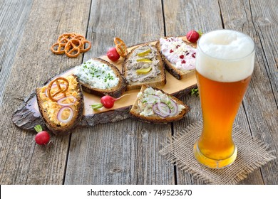 Hearty snack with different kinds of spreads on farmhouse bread served with a fresh yeast wheat beer on an old wooden table