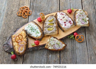 Hearty snack with different kinds of spreads on farmhouse bread served on an old wooden table